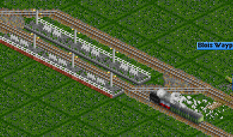 Train entering the station with mail van (white-red) in the head, with the locomotive boiler-forward...